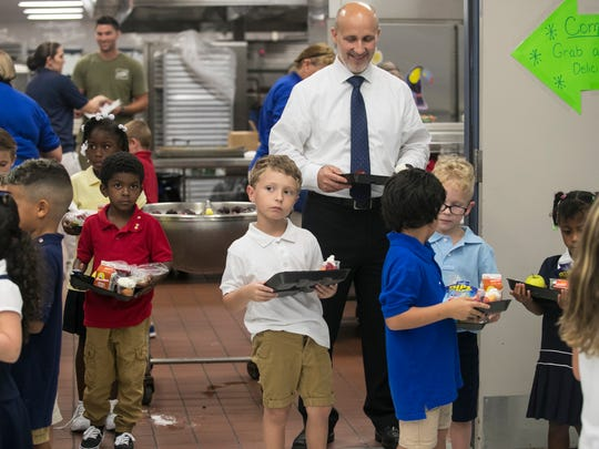 Lee County Schools superintendent Greg Adkins waits in line with Caloosa Elementary School students on Thursday, August 10, 2017, as they get lunch on the first day of school.
