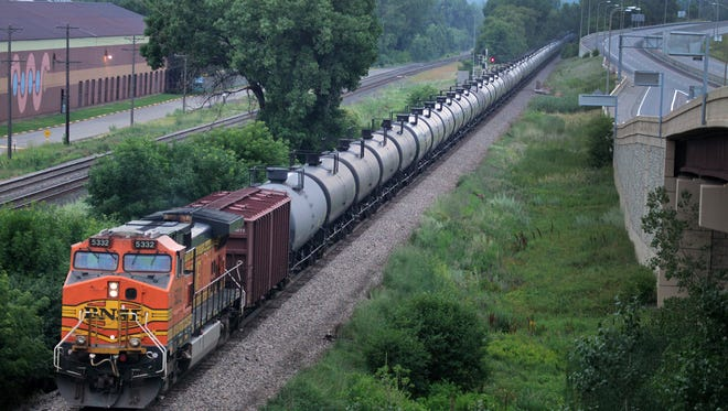 In this July 25, 2014 photo, an oil train moves through the area South of St Paul, Minn.  Railroad documents released by the state Department of Public Safety show about 50 trains carrying crude oil from North Dakota are passing through Minnesota each week.