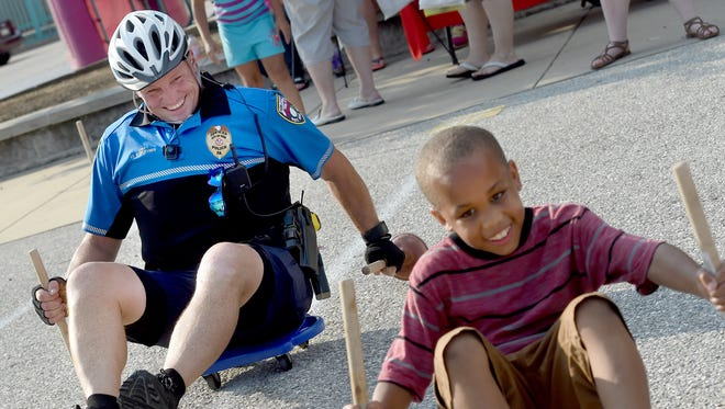 York City Police Lt. Erik Kleynen and 8-year-old Sincere Domnie are all smiles as the duo scooter race on the playground of Lincoln Charter School during National Night Out on Tuesday. The event is aimed at crime prevention and getting to know your neighbors.
