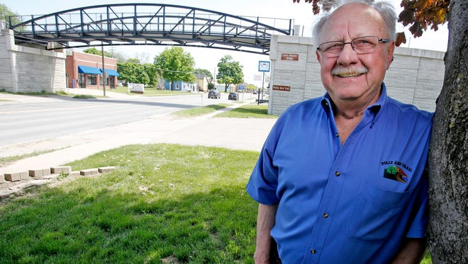 "Larry Obrecht stands near the Polly Ann Trail pedestrian overpass bridge that bears his name on May 24. He's to be honored Saturday for being the prime creator and fundraiser for the 17-mile ""rail trail"" in northern Oakland County."
