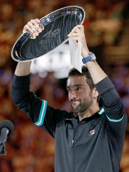 Croatia's Marin Cilic holds his runner-up trophy after losing to Switzerland's Roger Federer in the men's singles final at the Australian Open tennis championships in Melbourne, Australia, Sunday, Jan. 28, 2018. (AP Photo/Dita Alangkara)