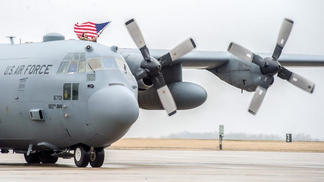 A member of the 182nd Airlift Wing waves an American flag as a C-130 transport plane taxis down the runway for a homecoming ceremony Thursday, March 12, 2020 for about 30 airmen returning from southwest Asia.