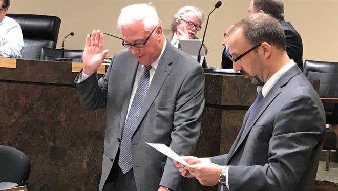 Paul Kelaher (left) takes the oath of office administered by Board Secretary Lou Alfano.