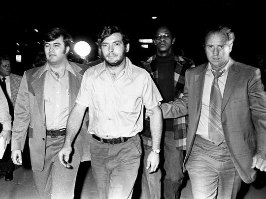 Metro Detective Sgt. Sherman Nickens, right, escorts Douglas Brown, middle, 21, of Greenbrier, Tenn., to the detective division Nov. 14, 1973. Brown, along with his brother, Roy, was interrogated for several hours about the murders of David (Stringbean) Akeman and his wife, Estelle. They were released from police custody and no charges were placed against the brothers.
