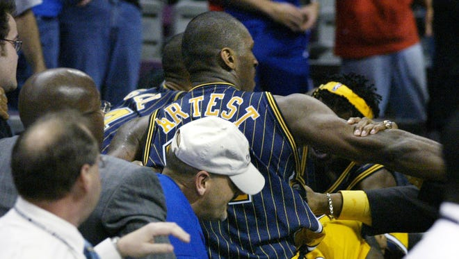 ** THIS ADDS THE NAME OF THE MAN BEHIND INDIANA PACERS RON ARTEST ** Indiana Pacers forward Ron Artest (91) goes into the stands during an altercation with fans Friday, Nov. 19, 2004, in Auburn Hills, Mich. Behind Artest, wearing a white hat, is John Green, of West Bloomfield Township, Mich. Green identified himself as the man behind Artest during a television interview.  (AP Photo/Duane Burleson)