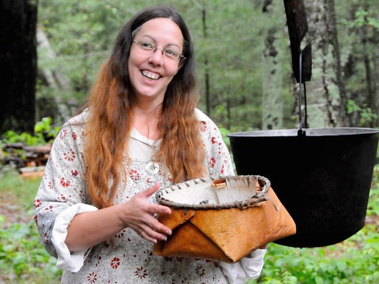 Krissy Kunshier, a docent at Forts Folle Avoine Historical Park, displays a birch-bark basket, a type used by the Ojibwe to hold dried wild rice 200 years ago.