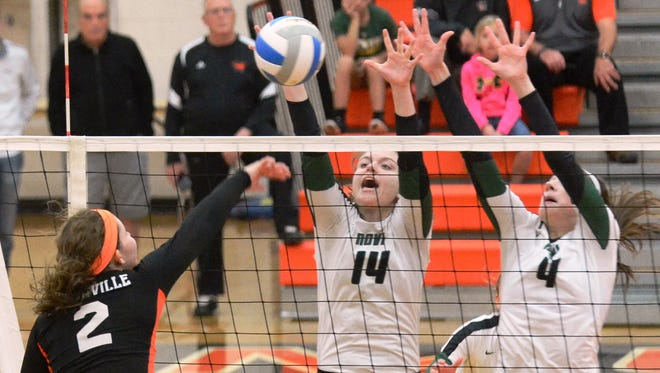 Novi's Erin O'Leary (14) and Emmy Robinson (4) team up for the block on Northville's Katie O'Malley (2) in Thursday's Class A district final.