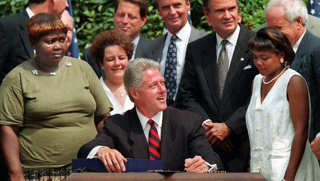President Bill Clinton, surrounded by former welfare recipients, signs legislation on Aug. 22, 1996, overhauling America's welfare system.