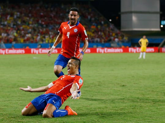 Chile's Mauricio Isla (4) watches as Alexis Sanchez celebrates after scoring his side's first goal during the first half of the group B World Cup soccer match between Chile and Australia in the Arena Pantanal in Cuiaba, Brazil, Friday, June 13, 2014.  (AP Photo/Kirsty Wigglesworth)