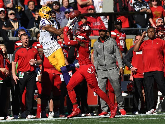 LSU wide receiver Malachi Dupre catches a pass as Louisville