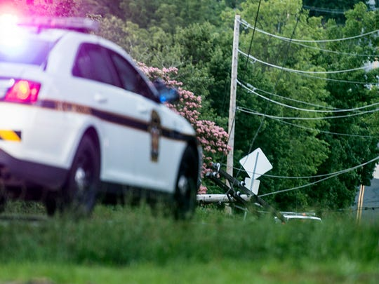 A utility pole is seen in the distance at the scene of a fatal crash on Cranberry Road in Tyrone Township on Sunday.