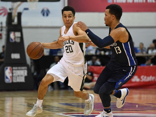 Milwaukee Bucks guard Travis Trice (20) dribbles away from Dallas Mavericks guard Jalen Brunson (13) during the second half at Cox Pavilion.