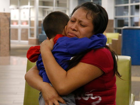 Maria holds her 4-year-old son Franco after he arrived