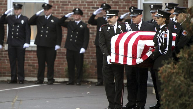 In this Dec. 31, 2015, file photo, Hamilton, Ohio, firefighters move the casket for Patrick Wolterman into an awaiting fire engine at the Hodapp Funeral Home in Cincinnati. A homeowner and his nephew are scheduled to go on trial in Ohio for murder in a 2015 house fire that resulted in the death of Hamilton firefighter Wolterman. Butler County Judge Greg Stephens said the court should try to seat a jury first. He set jury selection for Monday, Nov. 6.