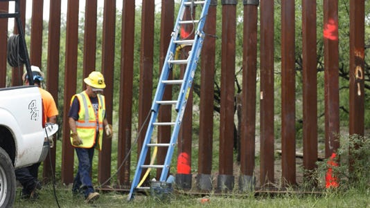 Workers make repairs to a section of the border fence near Nogales, Ariz.