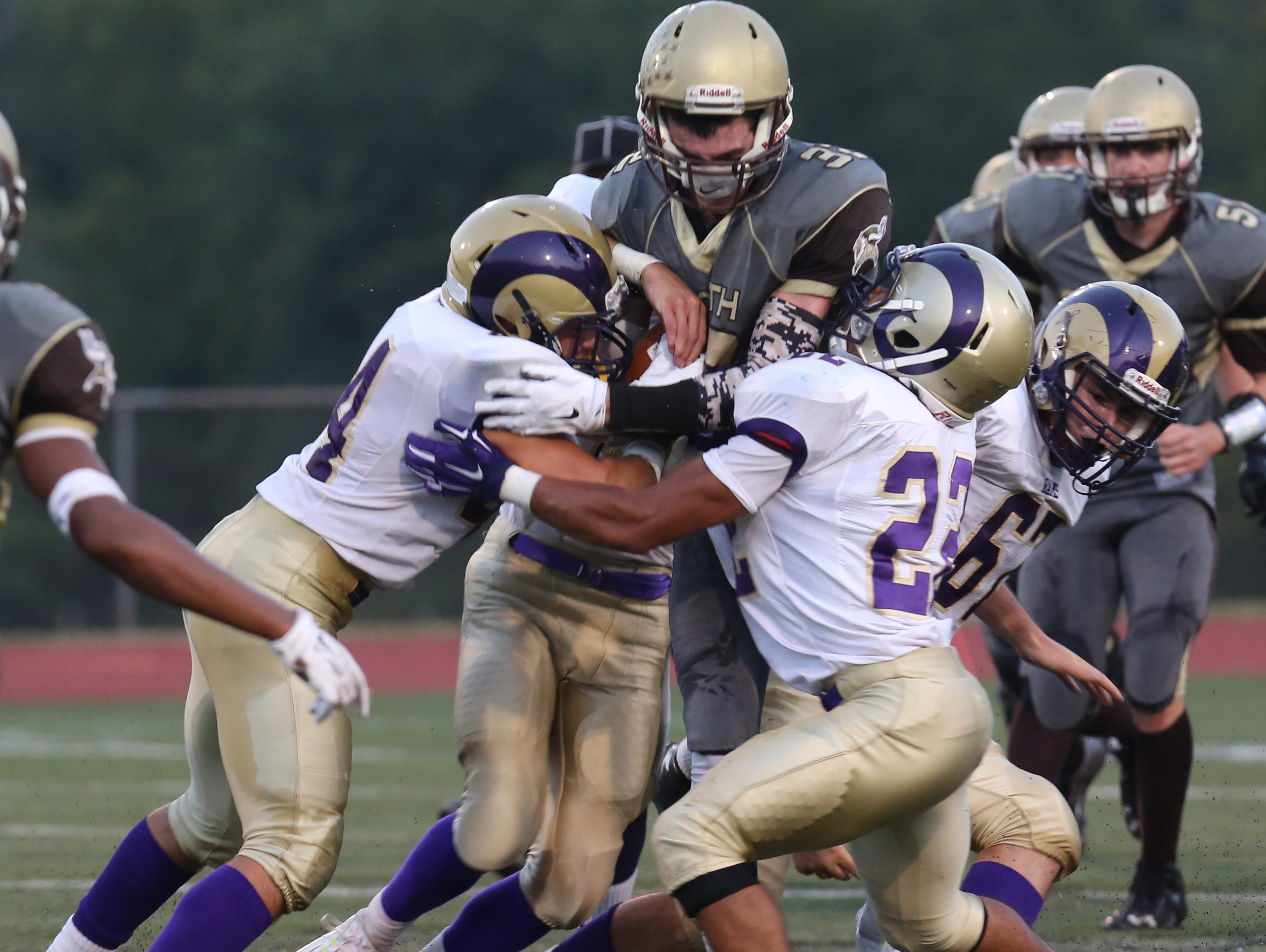 "Clarkstown South's Jack O""Shea (32) is tackled by Clarkstown North's defense during game action at Clarkstown South High School in West Nyack Sept. 4, 2015."