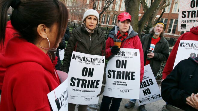 Chicago teachers and supporters gather to talk outside Amundsen High School in Chicago, Friday, April 1, 2016, during a one-day strike they say is aimed at getting lawmakers to adequately fund education and other programs in the nation's third-largest district.