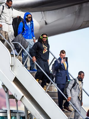 Members of the Seattle Seahawks including cornerback Richard Sherman, (top left in blue) and running back Marshawn Lynch (in front of Sherman) deplane after arriving at Sky Harbor International Airport on Sunday afternoon, Jan. 25, 2015.