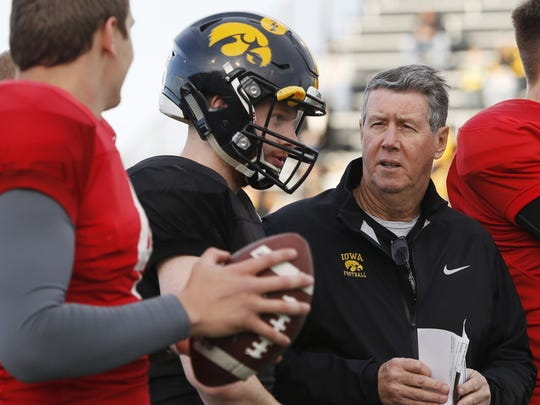 Quarterbacks coach Ken O'Keefe visits with Nathan Stanley, left, during Iowa's open practice April 7 at Valley Stadium in West Des Moines.