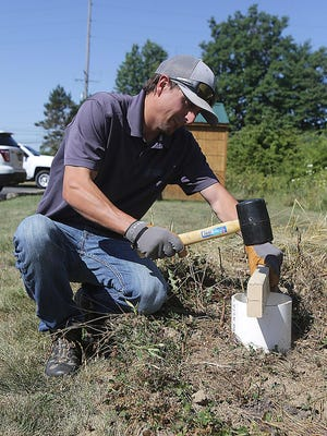 Jay Jordan, a natural resources technician with Stark Soil & Water Conservation District, hammers a 6-inch core into the ground, demonstrating how to extract a healthy soil sample. The soil district is hosting a healthiest soil competition in August.