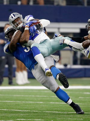 Lions DT A'Shawn Robinson body slams Cowboys RB Ezekiel Elliott (21) after making a stop on a run by Elliott in the second half Monday in Arlington, Texas. The Lions were penalized for the play.