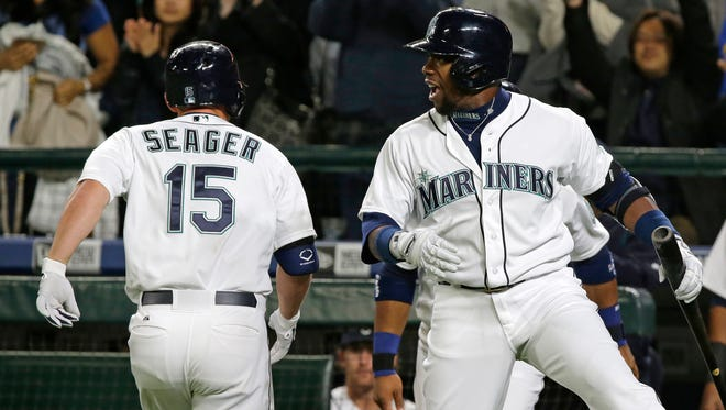 Seattle Mariners Kyle Seager (15) is greeted at the dugout by teammate Rickie Weeks after Seager hit a two-run home run against the Los Angeles Angels in the sixth inning of a baseball game, Wednesday, April 8, 2015, in Seattle.