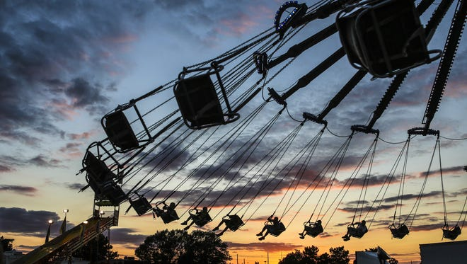 Children are silhouetted against a clear evening sky on the swing ride at the Kentucky State Fair in 2015.