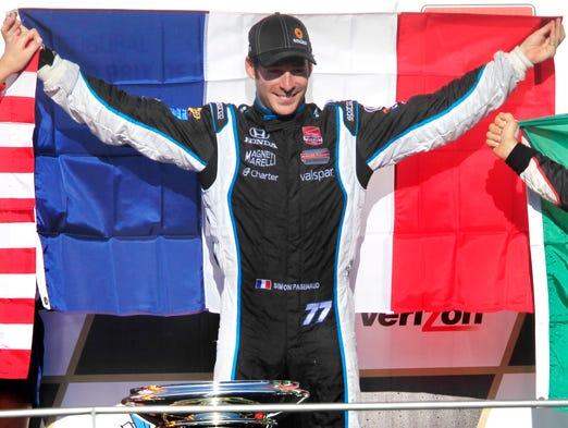 Simon Pagenaud holds up the flag of France on the victory stand after winning the inaugural Indianapolis Grand Prix at the Indianapolis Motor Speedway on Saturday, May 10, 2014.