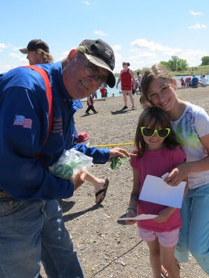 John R. Kelley of Walleyes Unlimited Montana gives two girls a bracelet at a 2013 Wadsworth Park Kids' Day event in Great Falls. Kelley died in 2014 and there is a monument in the park in his honor.