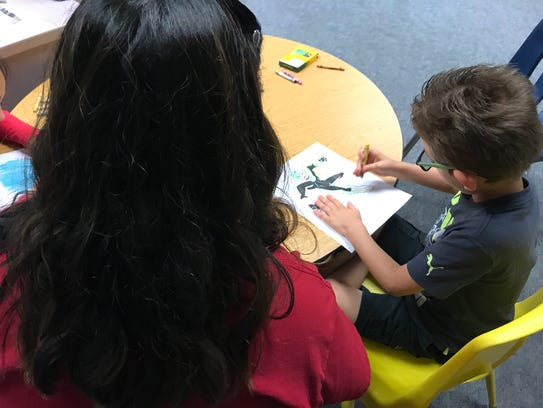 A teacher works one-on-one with a student during the