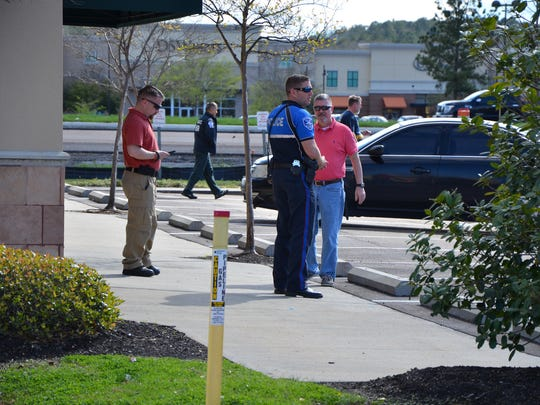 Law enforcement officers stand outside Ichiban Sushi