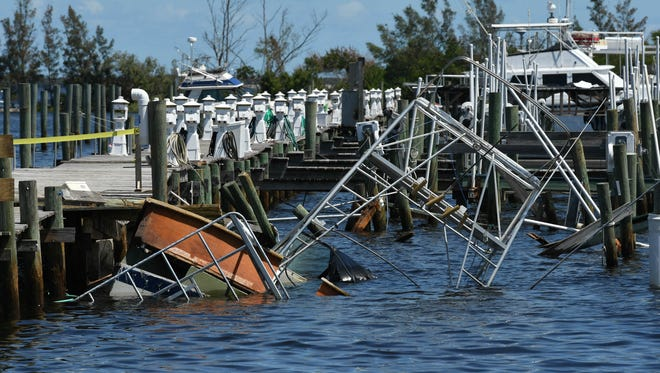 A capsized boat sits on the bottom ned to the dock at Fins Marina in Sebastian  Mandatory Credit: Craig Bailey/FLORIDA TODAY via USA TODAY NETWORK