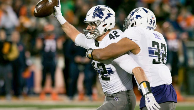 Northwestern linebacker Nate Hall (32) celebrates with linebacker Paddy Fisher (42) after Fisher's interception during the third quarter of the Wildcats' 42-7 win over Illinois on Saturday.
