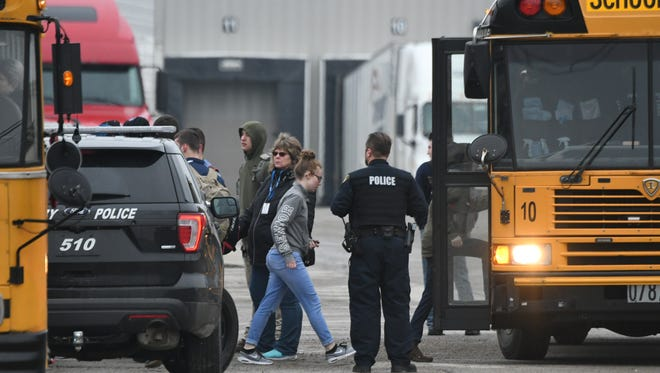 Students climb on buses to return to their home schools after Pioneer Career and Technology Center closed on Feb. 16 after a bomb threat was found in the building. Students were sent home shortly after they arrived.