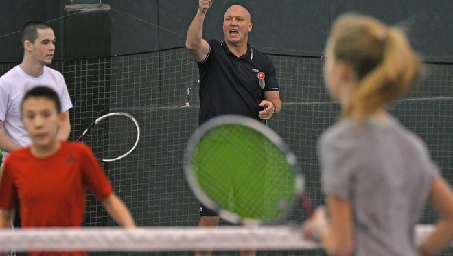 Former French Open doubles champ Luke Jensen shouts instructions while leading a clinic at Lakewood Racquet Club on Monday.