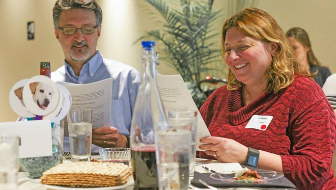"""Frank Impicciche, a priest with St. Matthew's Episcopal Church, left and his wife Susie Wolf, who is jewish, follow along with the reading of the Passover story, or """"Haggadah"""", during a inclusive interfaith family Seder held April 10 at Market District in Carmel,"""