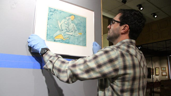 """Frankie Cruzeiro, a museum attendant at the Carlsbad Museum and Art Center, adjusted """"Virgo,"""" a work from Roderick Mead's """"Zodiac"""" print series, before hanging it."""
