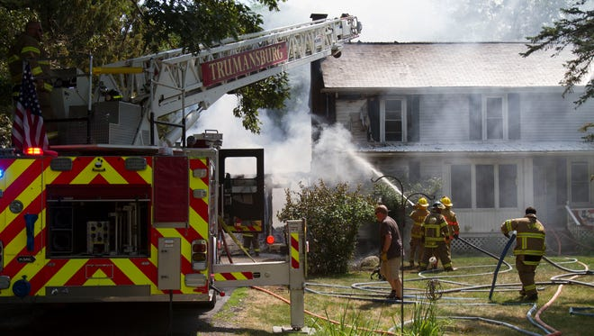 Firefighters work to extinguish a blaze Wednesday on Cayuga Street in Trumansburg. The fire destroyed a garage and killed a cat and dog.