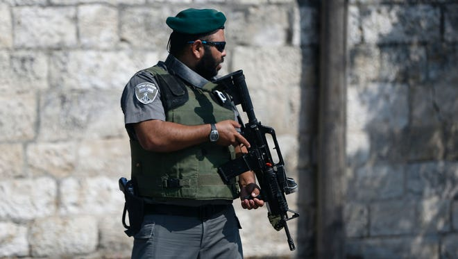 An Israeli policemen stands guard at the scene where police said a Jewish man was stabbed with a screwdriver in the East Jerusalem neighborhood of Al-Tur on Aug. 11, 2016.