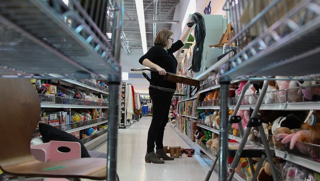 Natalie Greener, store manager of Cedar Hills Goodwill, stocks the shelves in new West Salem Goodwill location prior to grand opening.
