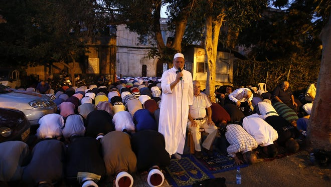 Palestinian Muslim worshippers gather to pray outside Jerusalem's Old City on July 25, 2017 as Muslim officials said worshippers should continue to boycott the Al-Aqsa mosque compound, even after Israel removed newly installed security measures that had triggered deadly violence. Israel removed metal detectors from a highly sensitive Jerusalem holy site after their installation triggered deadly violence, but Muslim officials said worshippers should continue a boycott for now. Israel installed metal detectors at entrances to the compound after an attack nearby that killed two policemen on July 14.