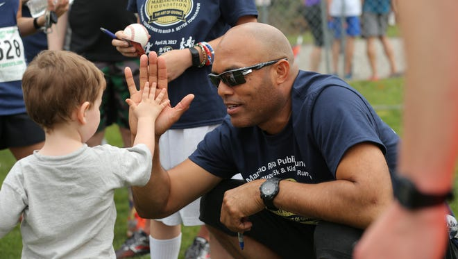 A young fan gets a high-five from future Hall of Fame pitcher Mariano Rivera at a 5K run in Pennsylvania last year. The event moves to Wilmington next month.