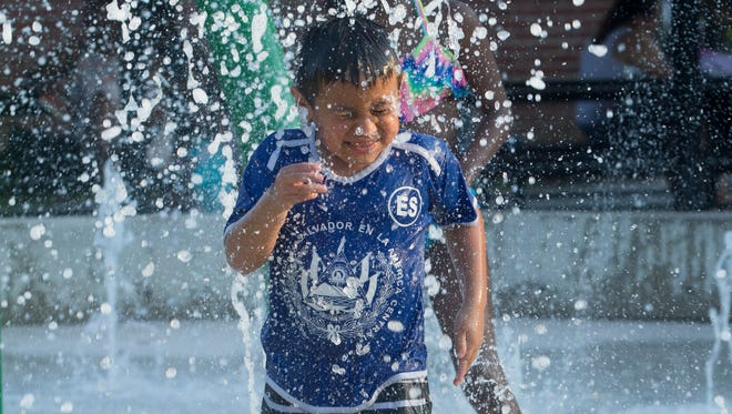 A child cools off in a water fountain in Washington, DC.