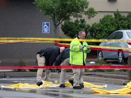 Boston police officers and detectives investigate at the scene of a shooting Tuesday morning, June 2, 2015) at 4600 Washington St. in Roslindale, Mass. A man under surveillance by terrorism investigators has been shot and killed by a Boston police officer. Police Commissioner William Evans confirmed from the scene that the man shot at about 7 a.m. at a pharmacy in the city's Roslindale neighborhood has died. Evans said the man was under surveillance by the Joint Terrorism task Force.  (Mark Garfinkel/The Boston Herald via AP)  BOSTON GLOBE OUT; METRO BOSTON OUT; MAGS OUT; ONLINE OUT