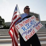 171536129.jpg WASHINGTON, DC - JUNE 26: Gay rights supporter Jay Norris, of New York City, holds a U.S. flag outside the U.S. Supreme Court building on June 26, 2013 in Washington, DC. The high court is expected to rule on the DOMA and Prop 8 gay marriage cases. (Photo by Win McNamee/Getty Images)