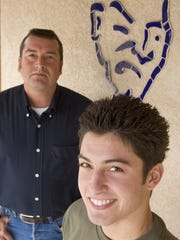 """DIGITAL -- 118196 -- 4corners -- 14 JANUARY 2005 -- YUMA, AZ: Mark Welter (CQ) left, and his son, Mark Welter, (CQ), are both Yuma Criminals, the younger Welter a current Criminal, the elder a past Criminal. The Welters are so proud of their Criminal affiliation that they inlaid the Criminal logo in tile on the wall  of their pool deck. The elder Welter said, """"If you went to Yuma High and graduated you bleed blue. Once a criminal always a criminal."""" AZR PHOTO BY JACK KURTZ"""