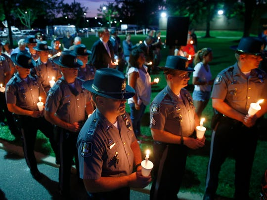 Wall Township police officers hold their candles outside the Monmouth County Police Academy Monday evening, July 11, 2016, during a remembrance of the 5 Dallas officers who were killed last week.  Photos of slain officers Brent Thompson (left) and Patrick Zamarripa are show in the background.