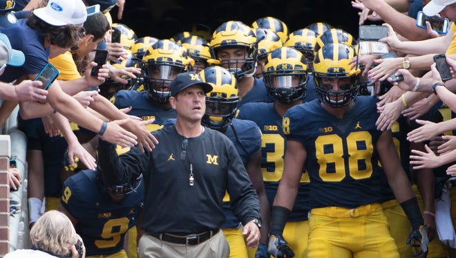 Michigan head coach Jim Harbaugh and his players walk out of the tunnel before Saturday's game.