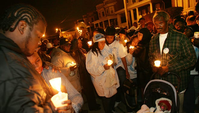 Family and friends of Charles Morris, who was shot to death Dec. 8 at 25th and West streets, gather four days later for a vigil at the crime scene.