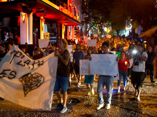 "Scores of local residents march carrying banners including ""Playa is Love,"" ""Peace for Playa,"" and ""No more pistols,"" toward the Blue Parrot club, where several people were killed in early morning gunfire, in Playa del Carmen, Mexico, Monday, Jan. 16, 2017. Deadly gunfire broke out in the crowded beachfront nightclub throbbing with electronic music before dawn on Monday, setting off a bloody stampede by screaming concertgoers at an international festival in this Caribbean resort."